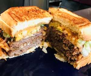 "The ""Big W"" - Two Burgers stacked between two Grilled Cheeses, lettuce, onions, cheese & thousand island dressing."